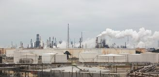 一个炼油厂的全景有发烟性的抽烟在灰色多云天空下 库存图片
