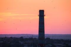 一个烟囱的剪影有飞鸟的在日落 五颜六色的红色天空 行业横向 库存图片