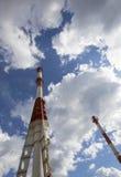 一个烧煤发电站的管子反对多云天空的背景的 免版税库存照片