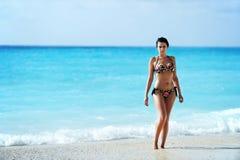 一个热带异乎寻常的海滩的性感的深色的妇女 免版税库存图片
