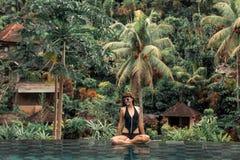 一个热带无限水池的愉快的少妇 巴厘岛的豪华旅游胜地 免版税图库摄影