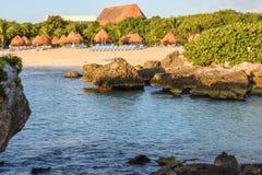一个热带沙滩的看法与秸杆伞、休息室绿色植被和珊瑚礁岩石的 库存图片