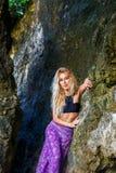 一个热带海岛的岩石的年轻美丽的白肤金发的女孩 库存图片