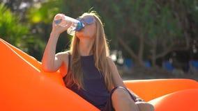 一个热带海滩的年轻女人坐一个可膨胀的沙发并且喝从一个多能用的塑料瓶的水 ?? 影视素材