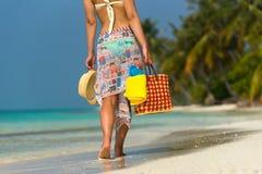 一个热带海滩的妇女与橙色袋子 免版税库存图片