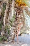 一个热带海滩的美丽的少妇在棕榈树附近 免版税库存照片