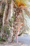 一个热带海滩的美丽的少妇在棕榈树附近 免版税图库摄影