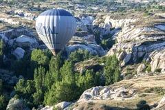 一个热空气气球在土耳其的卡帕多细亚地区飞行在爱谷下在日出在Goreme附近 免版税库存图片