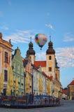 一个热空气气球飞行在城市Telc的大广场并且临近耶稣教会Kostel Jmena Jezis的名字两个塔  库存照片