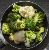 一个煎锅的顶视图有新鲜的被除霜的菜的:花椰菜,硬花甘蓝,抱子甘蓝 库存照片