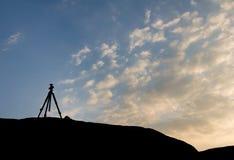 一个照相机三脚架的剪影有日落天空的 库存照片