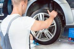 一个熟练的汽车机械师的手的低角度视图拿着轮胎的 免版税库存照片