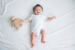 一个爬行的婴孩的画象在床上的在她的屋子里,可爱的男婴在白色晴朗的卧室,放松在床上的婴儿 免版税图库摄影