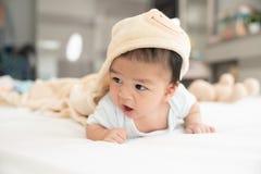 一个爬行的婴孩的画象在床上的在她的屋子里,可爱的男婴在白色晴朗的卧室,放松在床上的婴儿 免版税库存图片