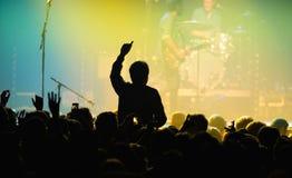 一个爱好者的剪影从观众的在一个音乐会在活力阶段 免版税库存图片