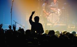 一个爱好者的剪影从观众的在一个音乐会在活力阶段 库存图片