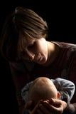 一个爱恋的母亲和婴孩的黑暗的画象 免版税库存图片
