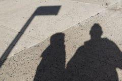 一个父亲和他的儿子的阴影在一条粗砺的具体街道上 免版税库存图片