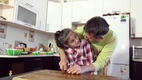 一个父亲在厨房教他的女儿切开与刀子的菜 股票录像