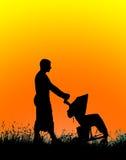 一个父亲的剪影有一个婴儿车的在日落 免版税库存照片