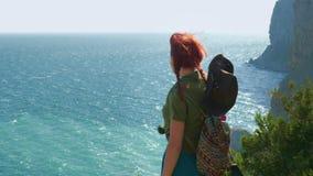 一个牛仔帽的年轻红发女孩旅客有背包的站立在山和神色顶部在蓝色海 股票录像