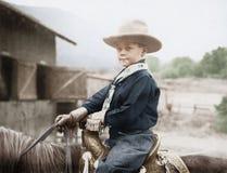 一个牛仔帽的男孩在马(所有人被描述不更长生存,并且庄园不存在 供应商保单那里w 免版税图库摄影