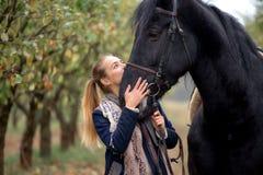一个牛仔帽的美丽的时髦的女孩有走在秋天森林里的马的,乡村模式 库存图片