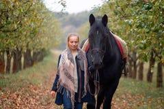 一个牛仔帽的美丽的时髦的女孩有走在秋天森林里的马的,乡村模式 免版税库存图片