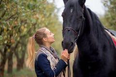 一个牛仔帽的美丽的时髦的女孩有走在秋天森林里的马的,乡村模式 库存照片