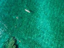 一个独木舟的鸟瞰图在漂浮在透明海的水中 海上的沐浴者 赞布罗内,卡拉布里亚,意大利 免版税库存图片