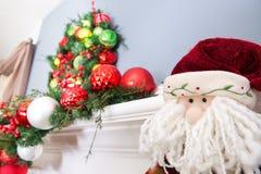 一个玩具圣诞老人的羊毛制面孔在花圈下的 库存照片