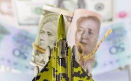 一个玩具的航空器战斗机在堆的美元票据和瓷 免版税库存图片