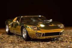 一个玩具GT40浅滩的再生产在沙子背景的 库存照片