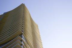 一个现代公司大厦的顶部的侧视图以在每个地板的淡黄色突出物 免版税库存图片