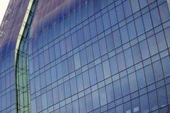 一个现代和典雅的法人大厦的弯曲的蓝色玻璃窗墙壁的近景 免版税库存照片