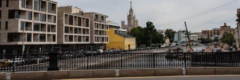 一个现代城市的日常生活 从桥梁的看法到沿江边的路,驾驶很多汽车 建筑和 免版税库存图片