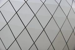 一个现代大厦的一个圆门面的细节由夹心板做成在蓝天背景 库存照片