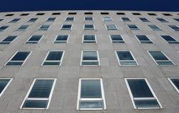 一个现代大厦的灰色石门面与从下面被看见的许多窗口的 库存照片