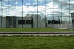 一个现代大厦的绿色草坪和玻璃门面 免版税库存照片