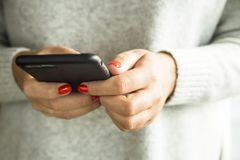 一个现代女孩通过智能手机使用互联网 免版税库存图片
