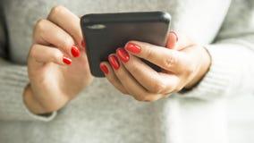 一个现代女孩通过智能手机使用互联网 免版税图库摄影