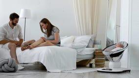 一个现代年轻家庭的概念 丈夫带来他的妻子咖啡供住宿,并且他们的孩子在a旁边睡觉 股票视频