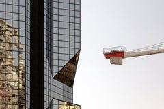 一个现代玻璃大厦和一个历史建筑和起重机的反射 免版税图库摄影