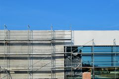 一个现代购物中心的建筑与玻璃和混凝土门面和地下停车处的,在与蓝色的一个晴天 图库摄影