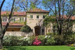 一个现代高级灰泥房子的入口在有桃红色和白色azeleas和树的春天离开开始发芽  免版税库存照片