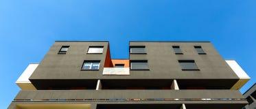 一个现代黑公寓的外部在蓝天后面的 免版税库存照片