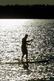一个现出轮廓的人桨搭乘的特写镜头在Saskatchewan湖的 免版税库存图片