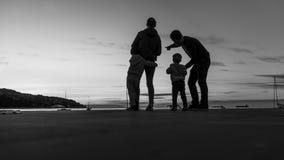 一个现出轮廓的家庭的灰度的图象户外 免版税库存照片