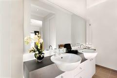 一个现代卫生间的接近的看法包括大镜子和白色 库存图片