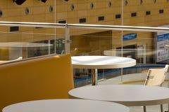 一个现代咖啡馆大阳台的看法与空的桌adn椅子的在a 免版税库存图片